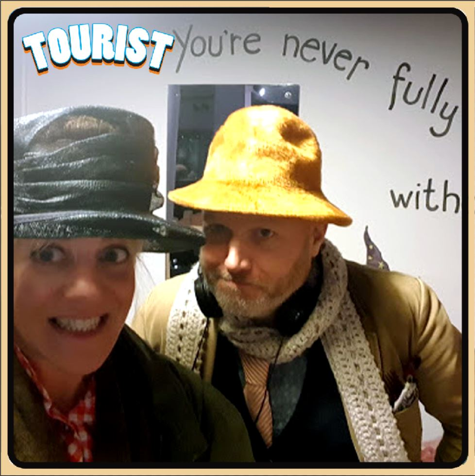 an photo of two people who are looking directoly at the camera. The photo shows the people from the shoulder up. A man is on the right and a women on the left. They are both wearing strange hats.